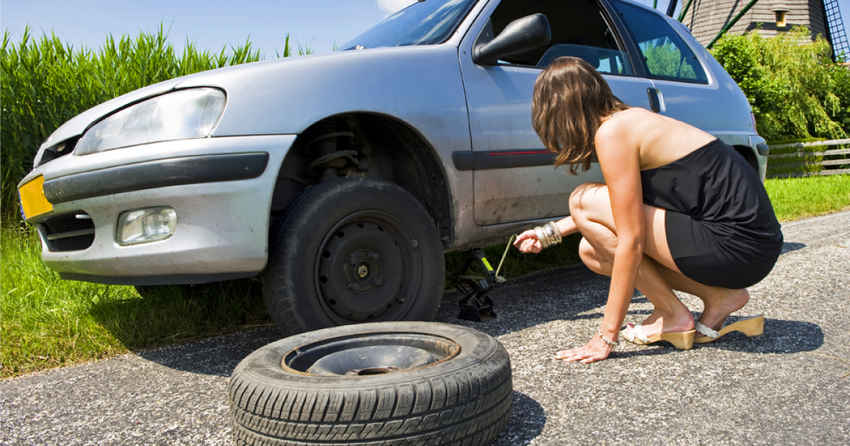 Девушка меняет колесо на машине